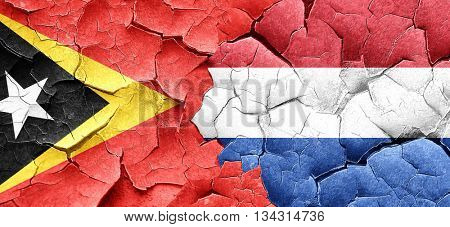 east timor flag with Netherlands flag on a grunge cracked wall