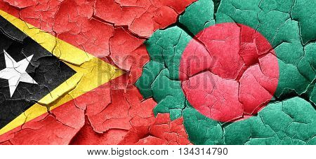 east timor flag with Bangladesh flag on a grunge cracked wall
