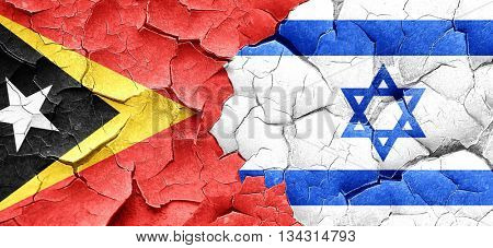 east timor flag with Israel flag on a grunge cracked wall