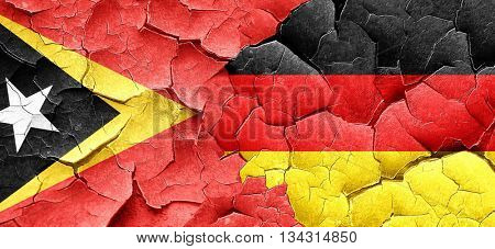 east timor flag with Germany flag on a grunge cracked wall
