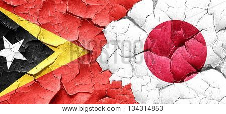 east timor flag with Japan flag on a grunge cracked wall