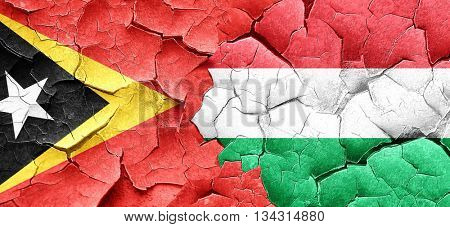 east timor flag with Hungary flag on a grunge cracked wall