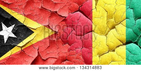 east timor flag with Guinea flag on a grunge cracked wall