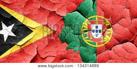 east timor flag with Portugal flag on a grunge cracked wall
