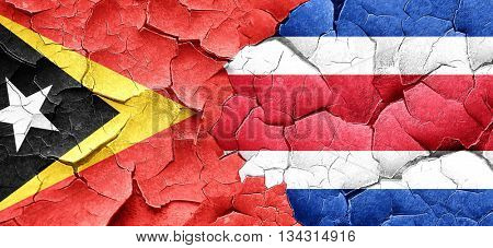 east timor flag with Costa Rica flag on a grunge cracked wall