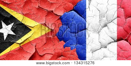 east timor flag with France flag on a grunge cracked wall