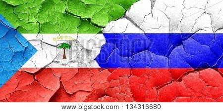 Equatorial guinea flag with Russia flag on a grunge cracked wall