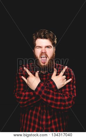 Happy guy winks showing his tongue with rock on hand gesture on a black blackground
