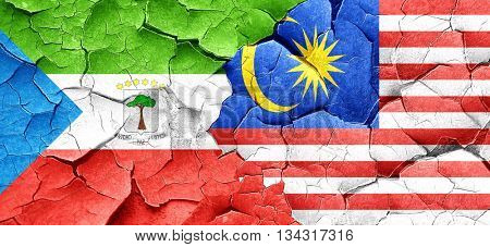Equatorial guinea flag with Malaysia flag on a grunge cracked wa
