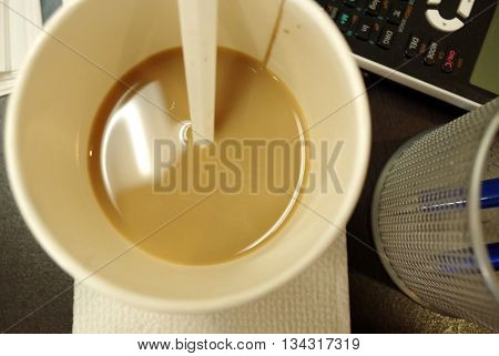 Cup of coffee, calculator and pen holder