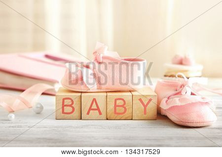 Baby booties on wooden bricks, closeup