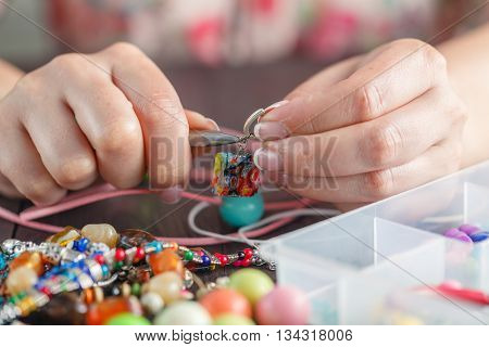 Homemade jewelry. Woman making home craft art bijouterie