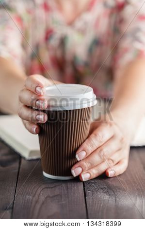Woman Holding Takeout Coffee At Table