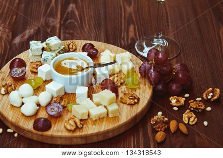 Cheese Board Served With Grapes And Nuts On A Wooden Background