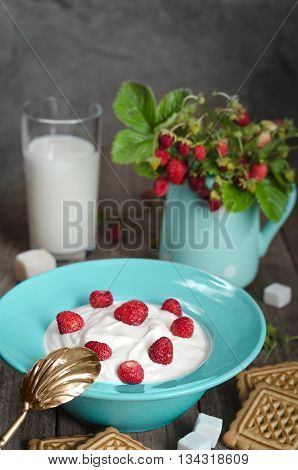 Strawberry with cream in a ceramic Cup, cookies and milk in glass on old wooden surface. Bouquet with strawberries in a ceramic vase and antique spoon In a rustic style.