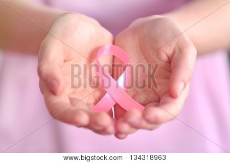 Woman holding pink ribbon. Cancer concept
