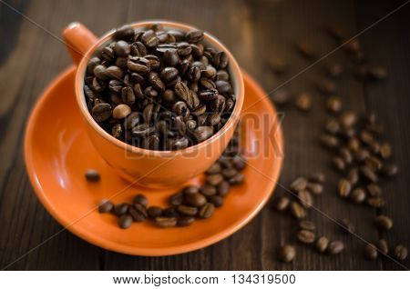 red cup with coffee beans on wooden table