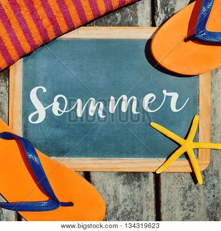 high-angle shot of a pair of orange flip-flops, a starfish, a beach towel and a chalkboard with the word sommer, summer in German written in it, on a rustic wooden boardwalk