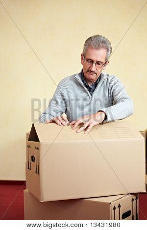 Elderly Man Opening Packing Case