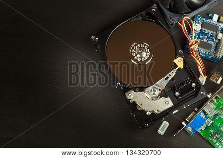 Open hard drive on a black wooden background. Production of computers. Electronics store. Backing up data on your computer. Modern technology. Place for your text.
