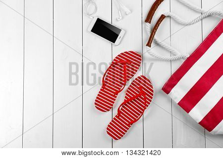 Beach accessories and phone on wooden background