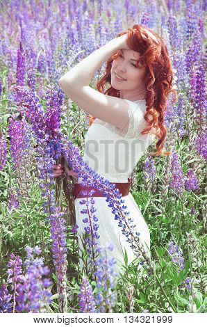 Redhead woman with curly long hair in summer lupine field