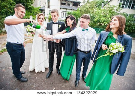 Groomsman And Bridesmaid Drinking Champagne On Wedding Party