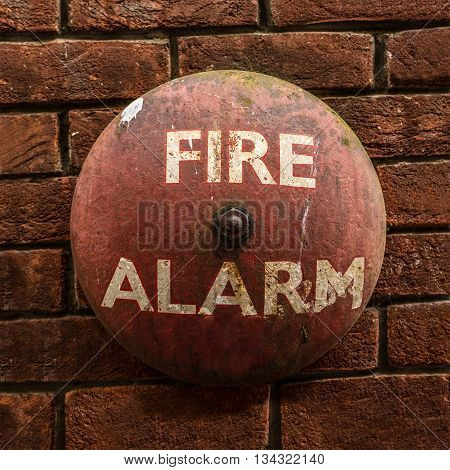 Rustic Vintage Fire Alarm Bell Against A Red Brick Wall
