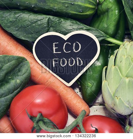 closeup of a heat-shaped chalkboard with the text eco food placed on a pile of some different raw vegetables, such as cucumbers, tomatoes, carrots or artichokes