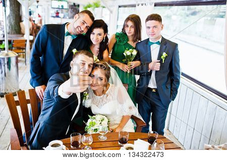 Happy Friends Of Wedding Couple And Groomsman With Bridesmaids At Cafe Make A Selfie