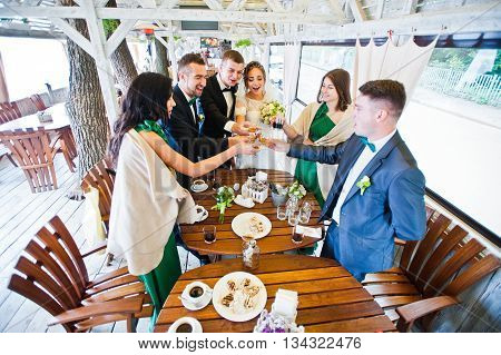 Happy Friends Of Wedding Couple And Groomsman With Bridesmaids At Cafe Cheers Glasses