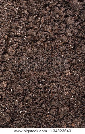 Black soil with fertilizer particles as a background