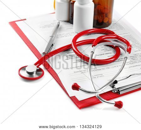 Red stethoscope and pills on white background