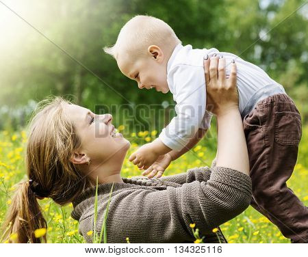 Happy family, mother lifts her son on nature background with sun rays