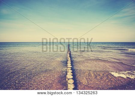 Retro old film stylized wooden breakwater in sea.