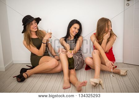 Three drunk girls drinking champagne at home.