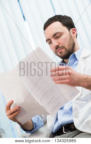 Male medicine doctor checking something at his papers. Medical care, insurance, prescription, paper work or career concept. Physician ready to examine patient and help