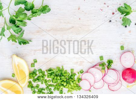 White wooden kitchen table background with healthy cooking ingredients and copy space. Vegetables and herbs for salad. Radish, spring onion, parsley, lemon. Top view