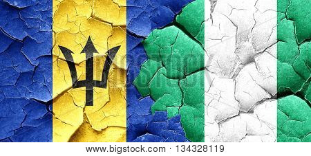 Barbados flag with Nigeria flag on a grunge cracked wall