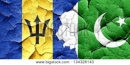 Barbados flag with Pakistan flag on a grunge cracked wall