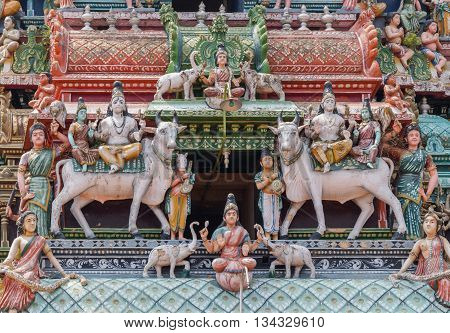 Chettinad India - October 17 2013:Detail of the Shiva temple gopuram at Kottaiyur shows twice Shiva and Parvati sitting on Nandi the bull. Above and beneath is Lakshmi showered by elephants. Combination of colorful statues.