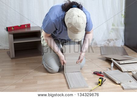 Assembling wooden furniture a woman glues part of the drawer sitting on the floor.