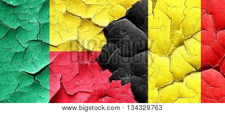 Benin flag with Belgium flag on a grunge cracked wall