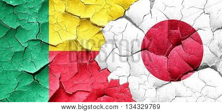 Benin flag with Japan flag on a grunge cracked wall