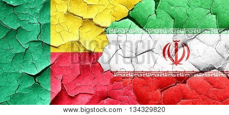 Benin flag with Iran flag on a grunge cracked wall