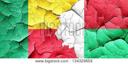 Benin flag with Madagascar flag on a grunge cracked wall