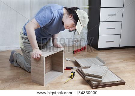 Woman connects together the board chipboard drawer assembly of furniture at home.