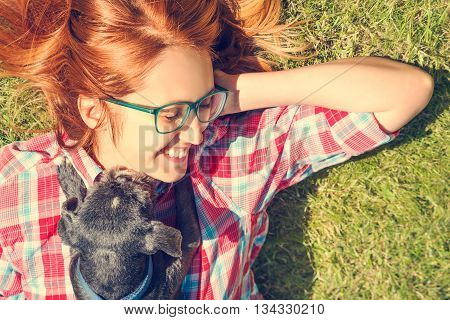 Little Dog and His Happy Owner Having Fun and Lying on Green Grass. Happy Girl and Shih Tzu Dog. Pets Love and Playing Concept. Toned Photo with Copy Space.