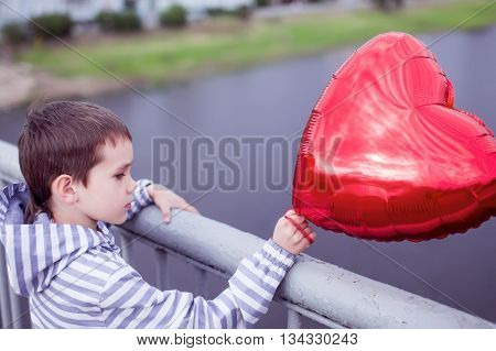 boy standing on the bridge and holding a red heart.  the concept of lost love. sad child with a balloon in the form of heart looking at the river from the bridge