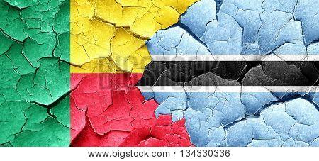Benin flag with Botswana flag on a grunge cracked wall